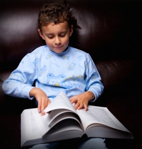 Cute kid reading a big book on a sofa